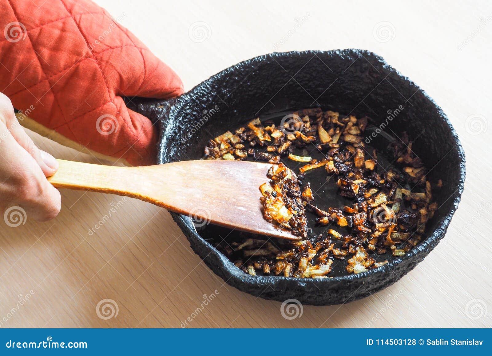 Overcooked cebula w niecce Zła kuchnia Pojęcie szkodliwy jedzenie i carcinogens