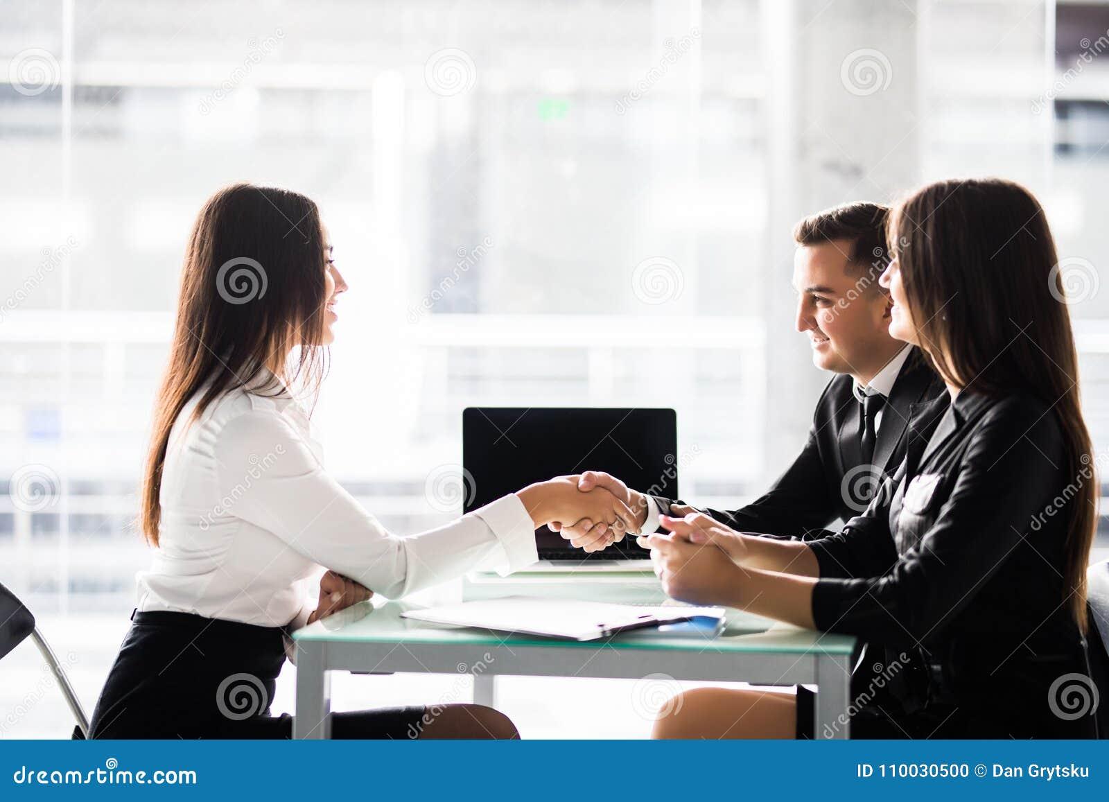 Overeenkomst Zijaanzicht van vrolijke jonge man zitting dicht bij zijn vrouw en het schudden hand aan vrouwenzitting voor hem bij