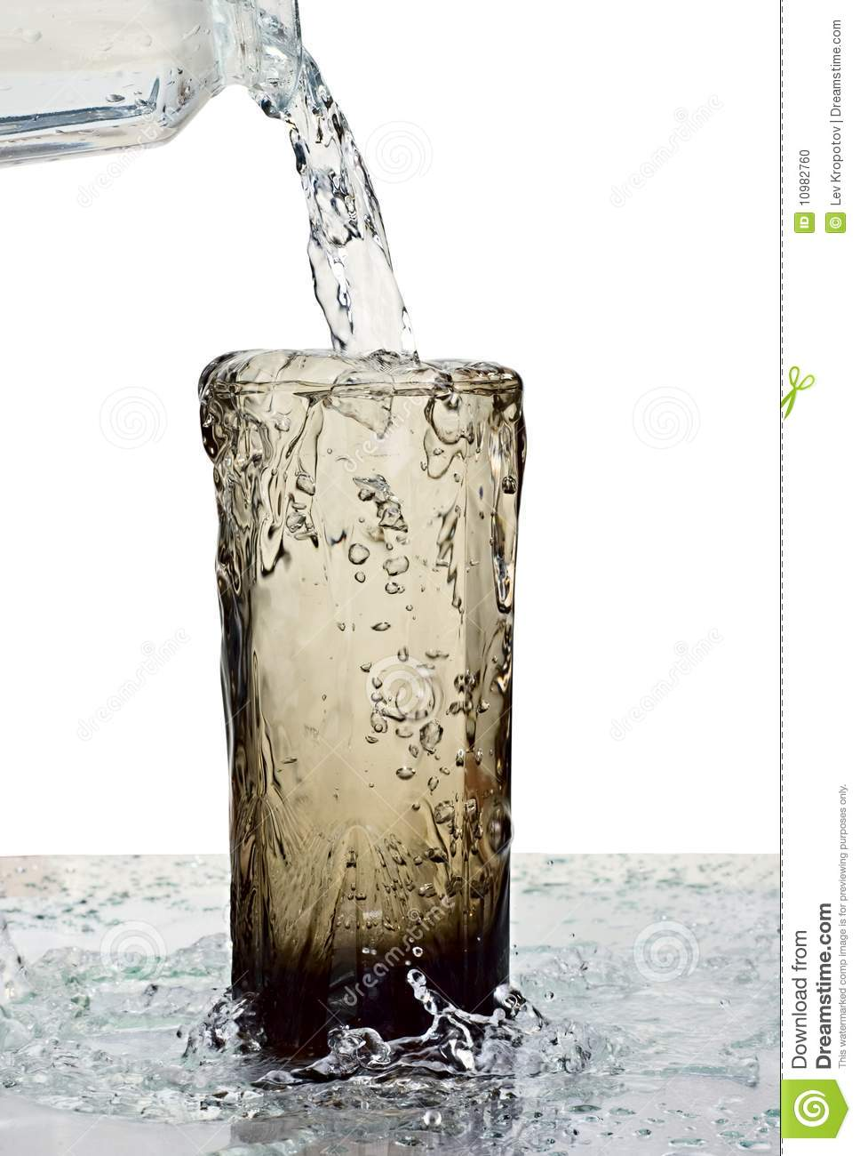 Glass of a water with overflow on white background.