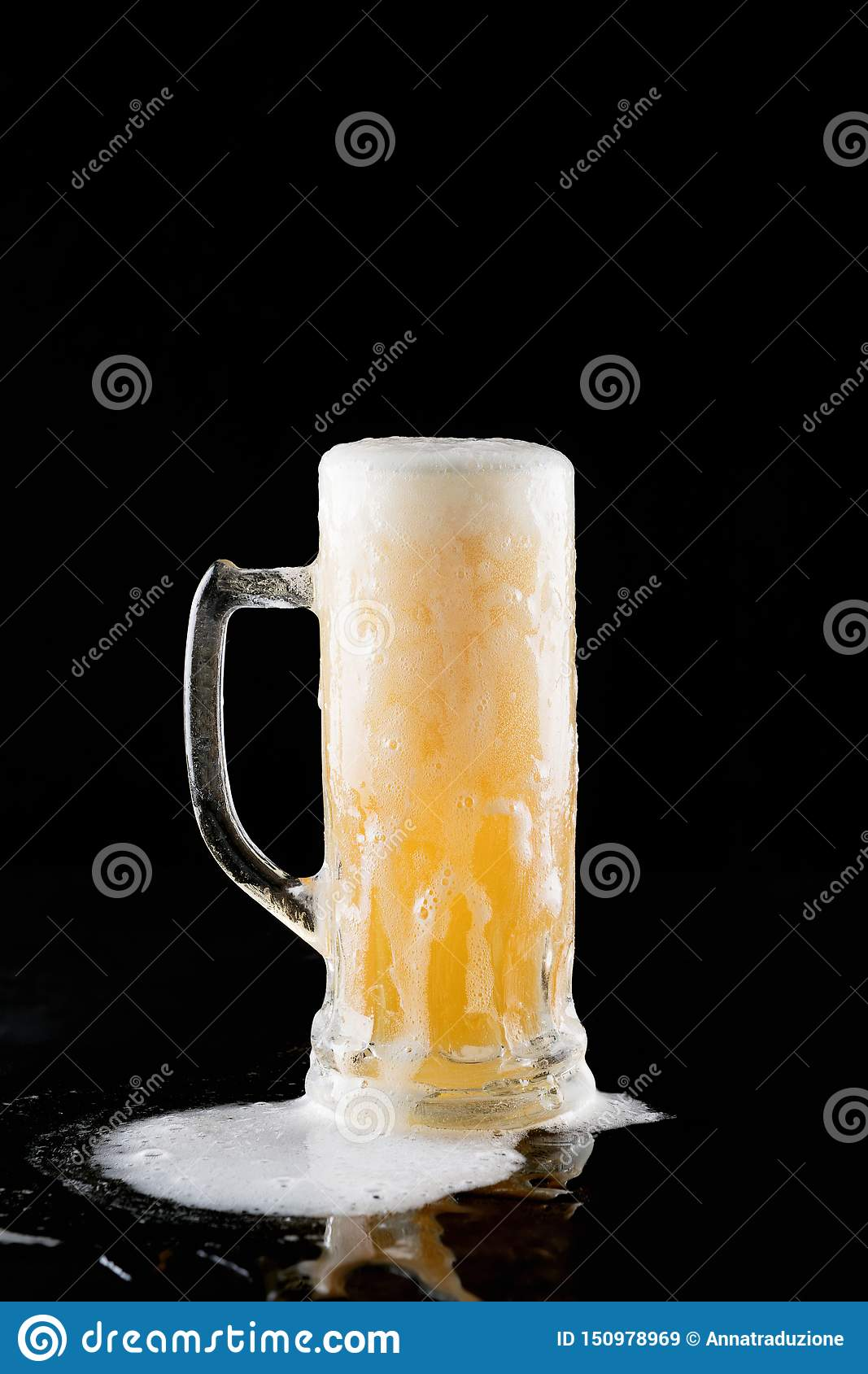 Overflowing mug of fresh cold light beer with froth flowing on the table and beautiful spilled beer on a black background with