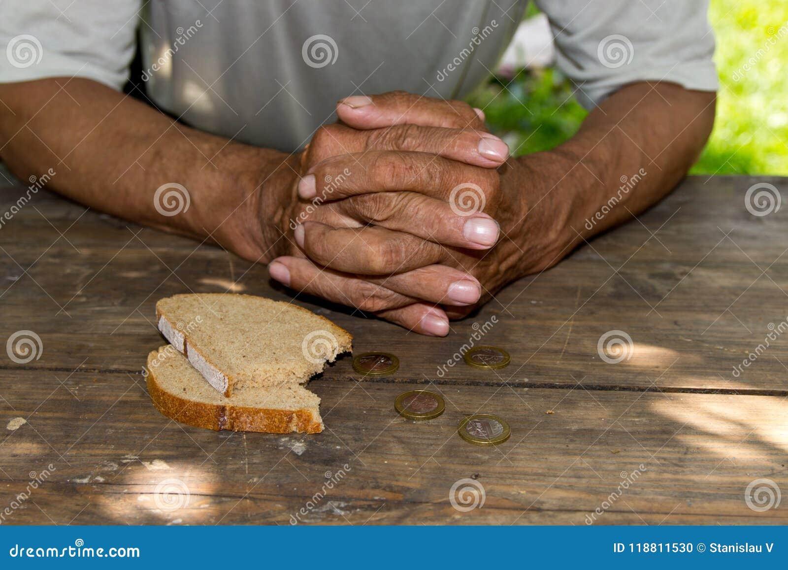 Overhandigt de slechte oude man ` s, stuk van brood en verandering, pence op houten achtergrond Het concept honger of armoede