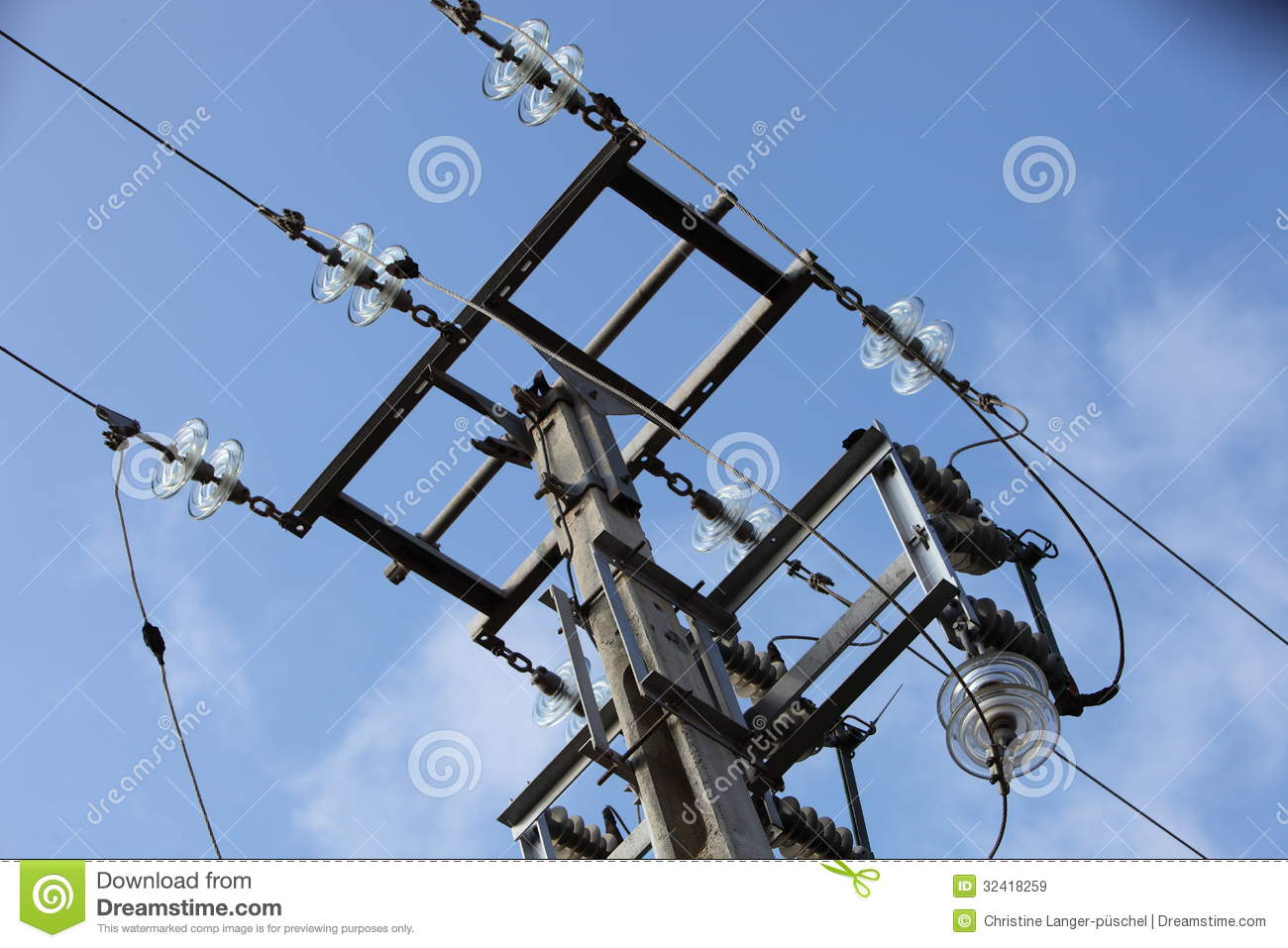 Overhead Electrical Conductors : Overhead electricity pole against a blue sky royalty free