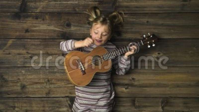 Overhead happy child girl on vintage wooden background playing ukulele  guitar Text or logo copy space Vertical top view
