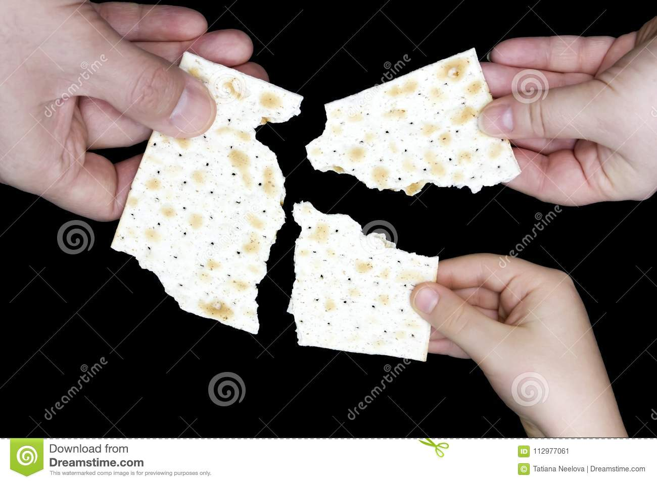 An overhead photo of Jewish child, woman and men hands hold matza, leavened bread isolated on black background. Hands holding matz