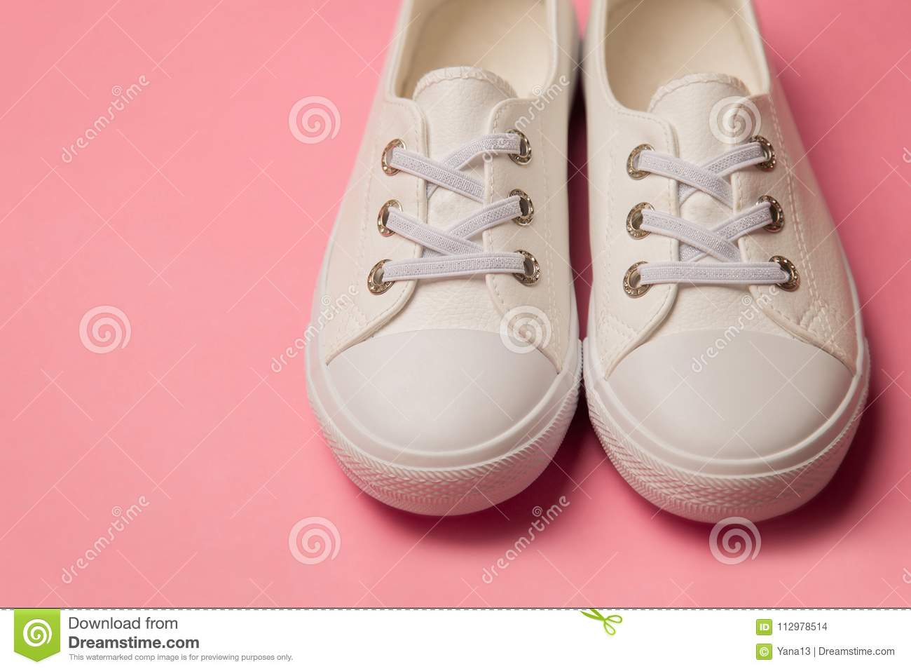 Overhead Shot Of White female Sneakers On Pastel Pink Background