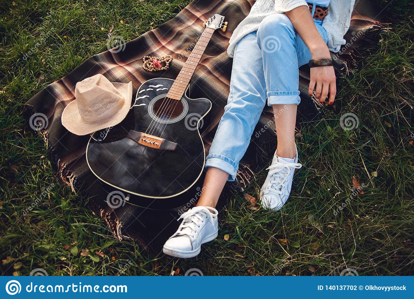 Overhead view of beautiful woman with guitar resting on green lawn. Top view