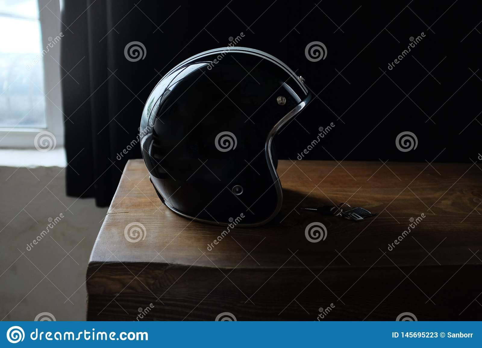 Overhead view of biker accessories placed on rustic wooden table. Items included motorcycle helmet, gloves, keys,. Motorcycle