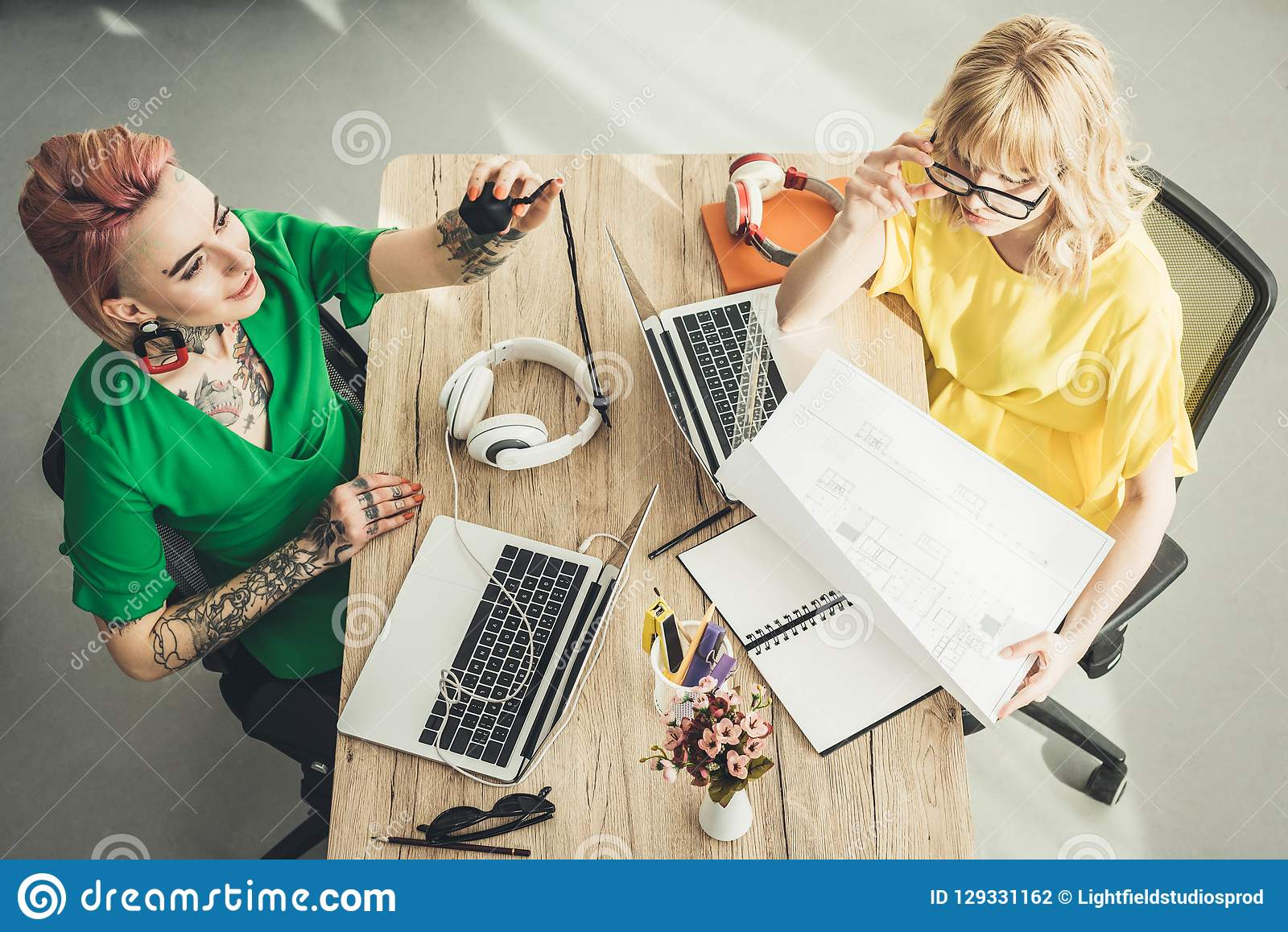 Overhead view of blogger and designer working at table together in office stock photography