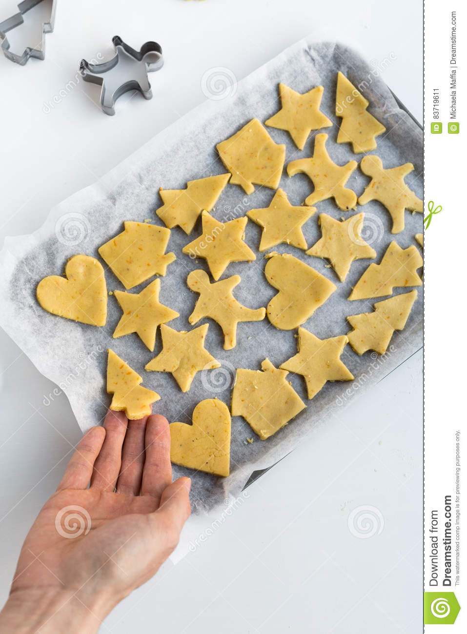 Overhead View Of Sweet Biscuit Dough Cut Into Festive Christmas Shapes On Baking Tray Stock Photo