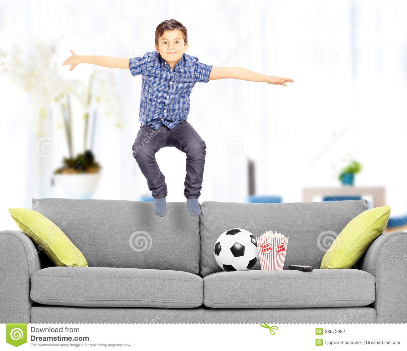 Overjoyed Boy Jumping On Couch At Home Stock Photography