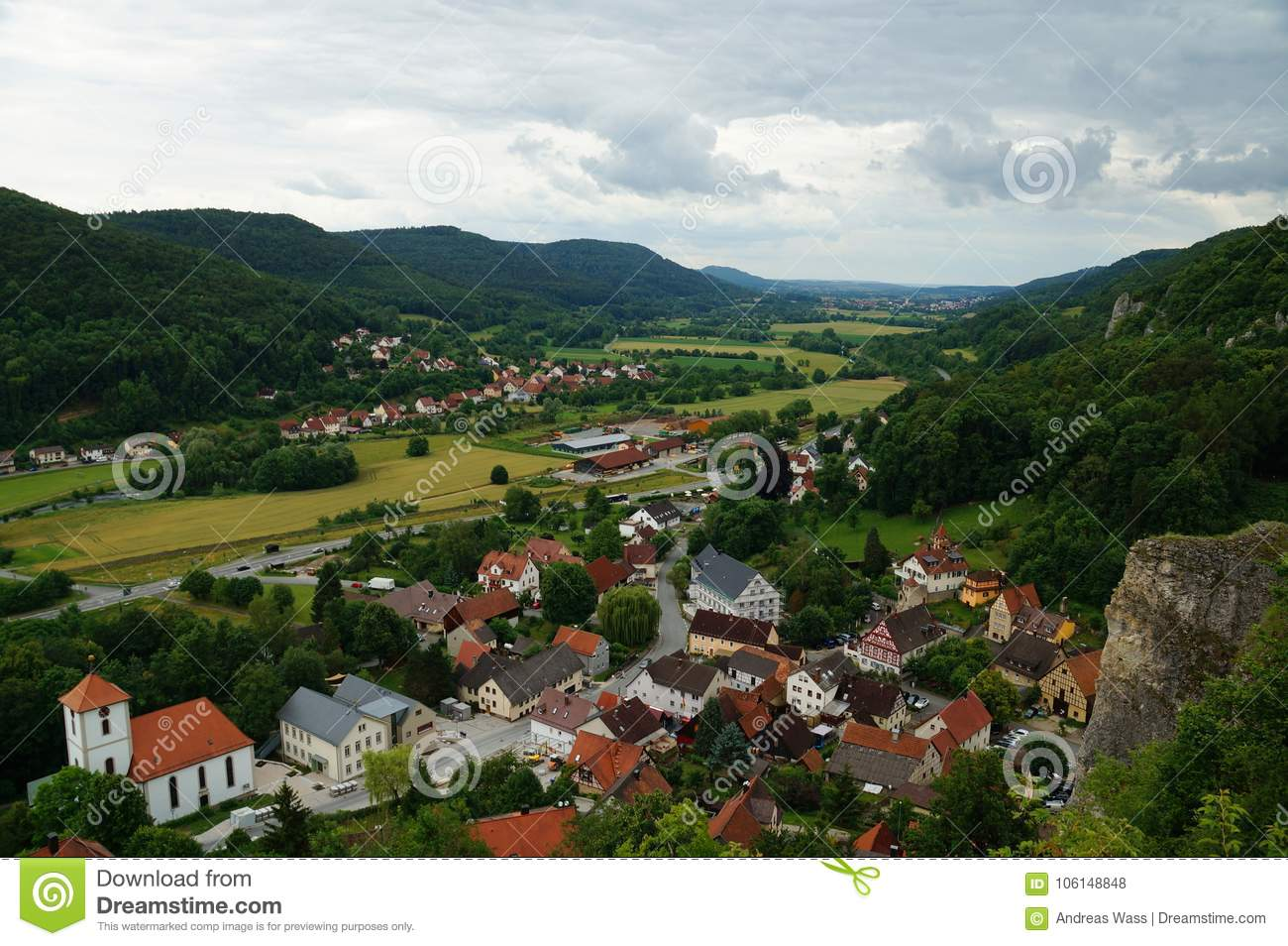 Colorful historic city in a green valley characterized by a river and fields in a karst landscape.
