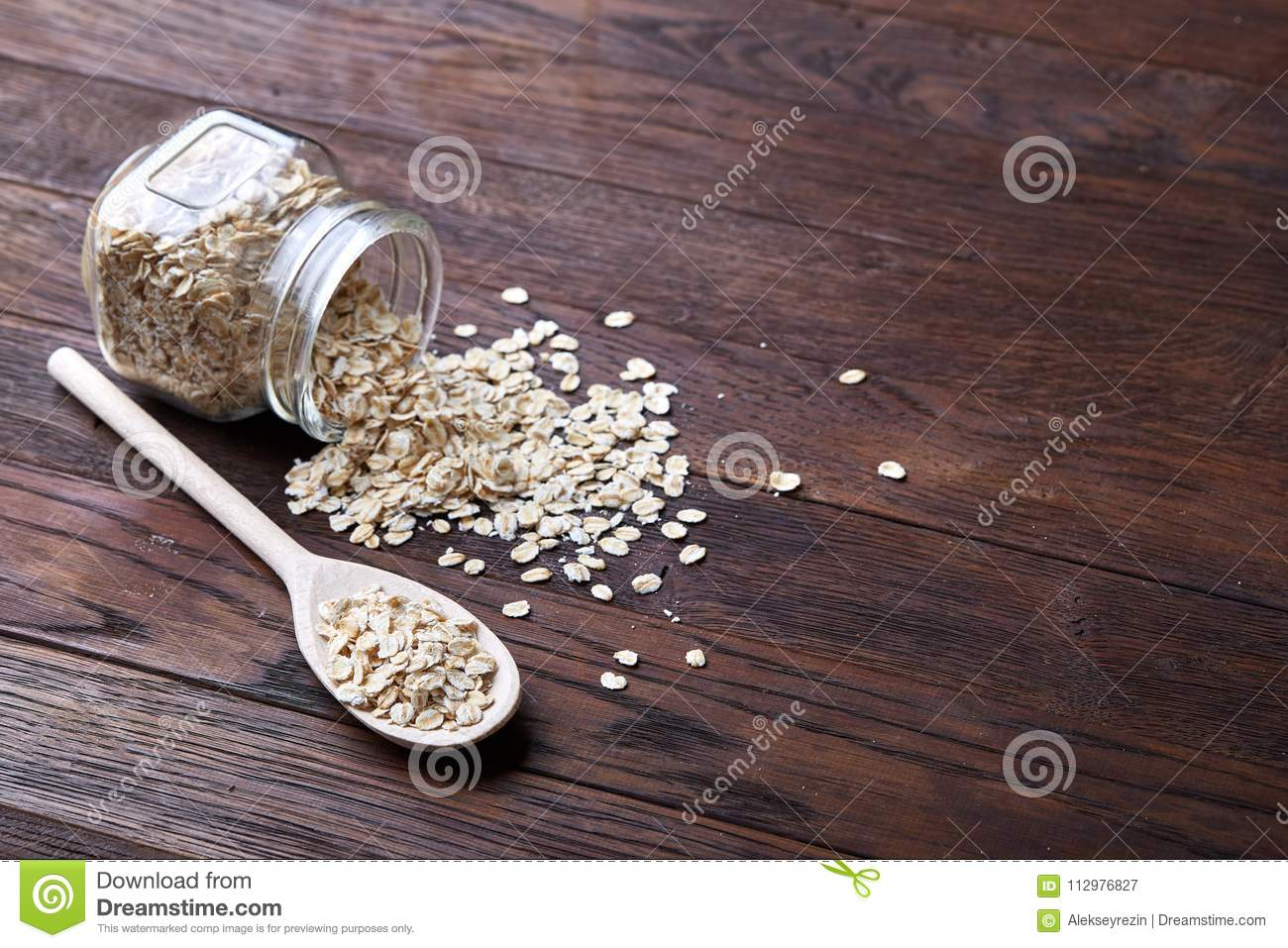 Overturned glass jar and spoon with raw oatmeal on vintage wooden background, close-up, selective focus.