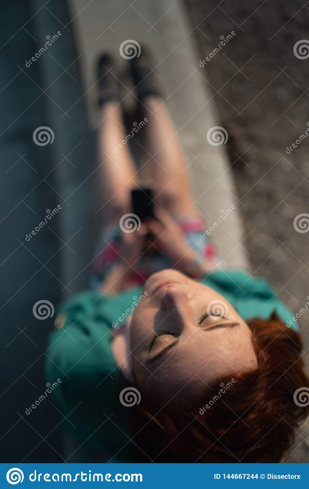 Overview of a young woman uses phone in a palace park sitting on a fountain - View from above
