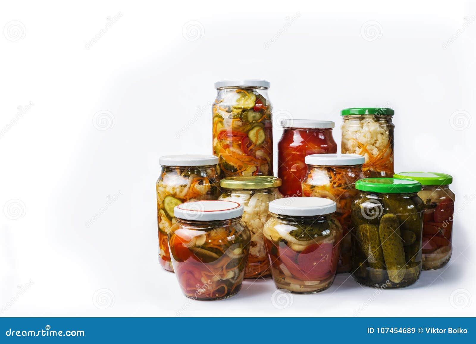 Overvloed van mooie glaskruiken met plantaardige eigengemaakte die salades op witte achtergrond wordt geïsoleerd