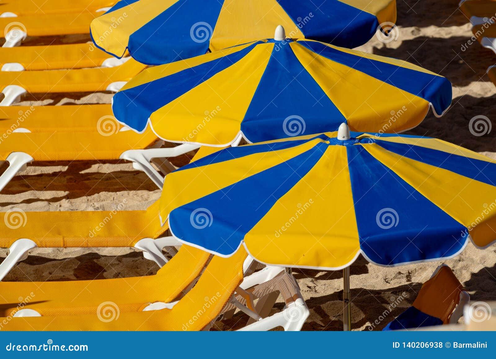Overvol strand met zonparaplu s en stoelen die op toeristen, betaald de dienst op stranden wachten