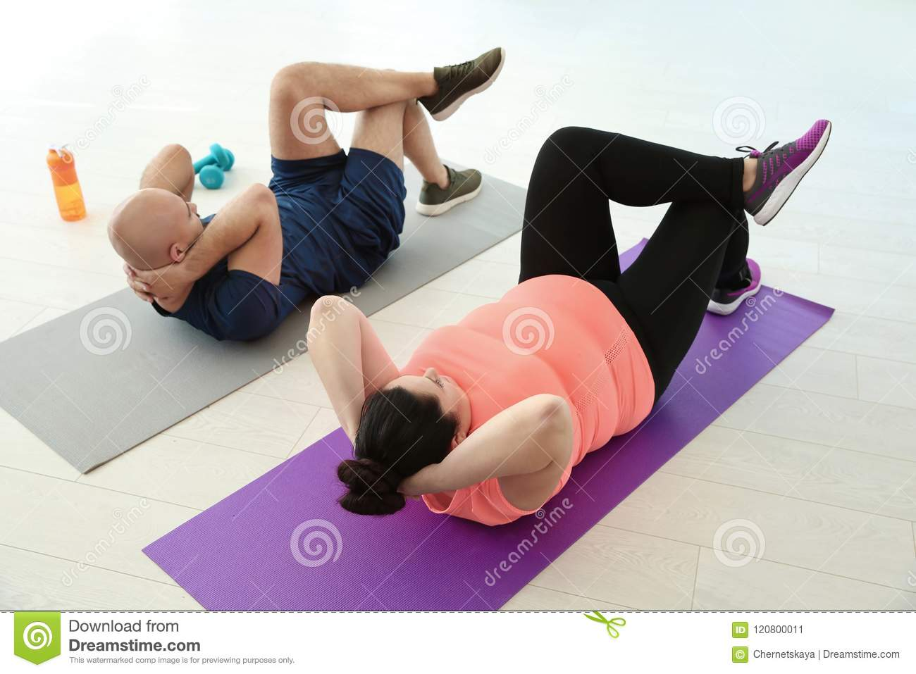 Overweight man and woman doing exercise on mats in gym stock image