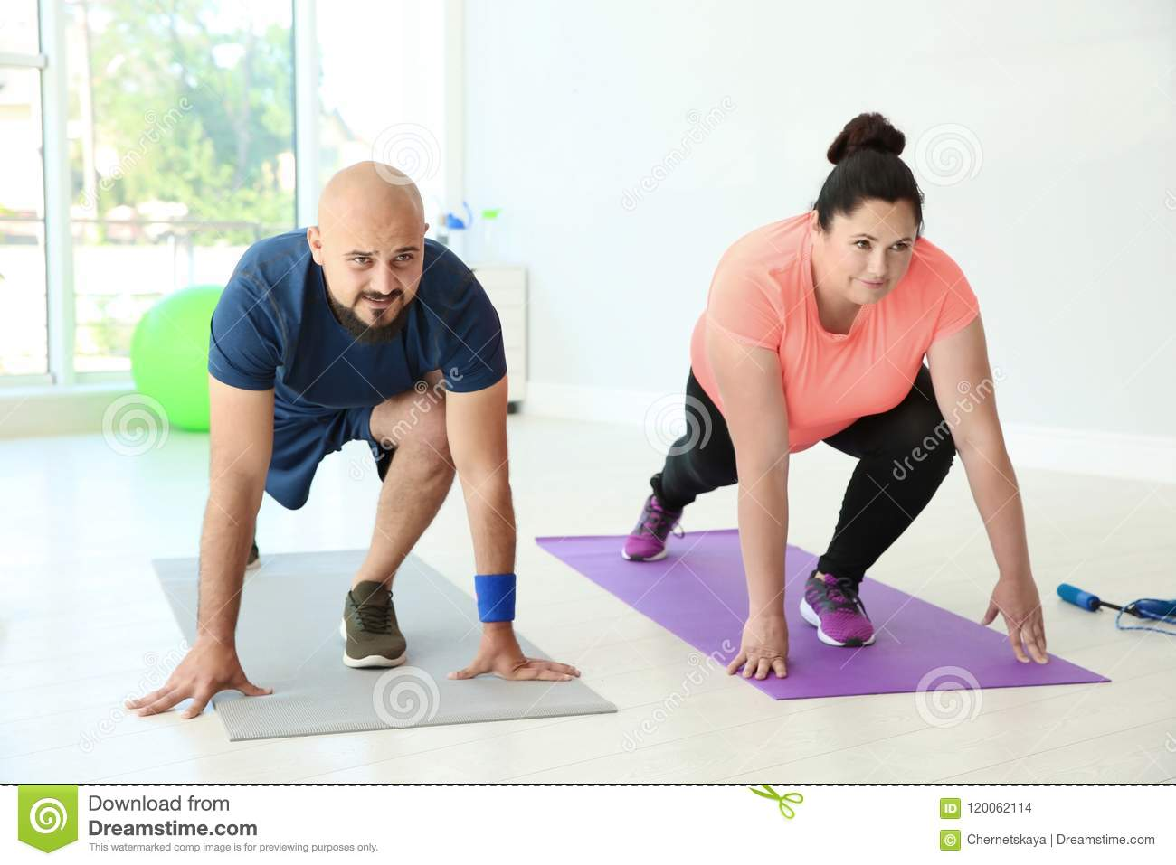 Overweight man and woman doing exercise stock photo image of