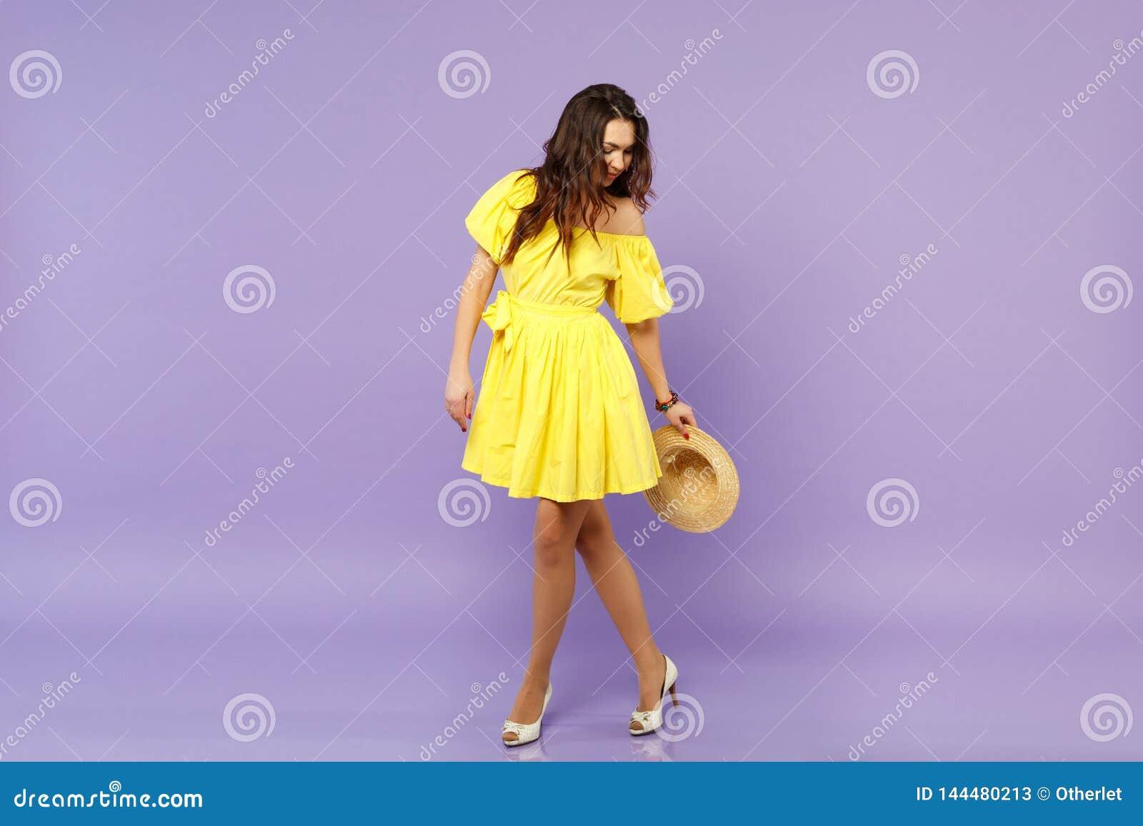 Overweldigend jonge vrouw in gele de zomerhoed van de kledingsholding, status, die onderaan geïsoleerd op pastelkleur kijken viol