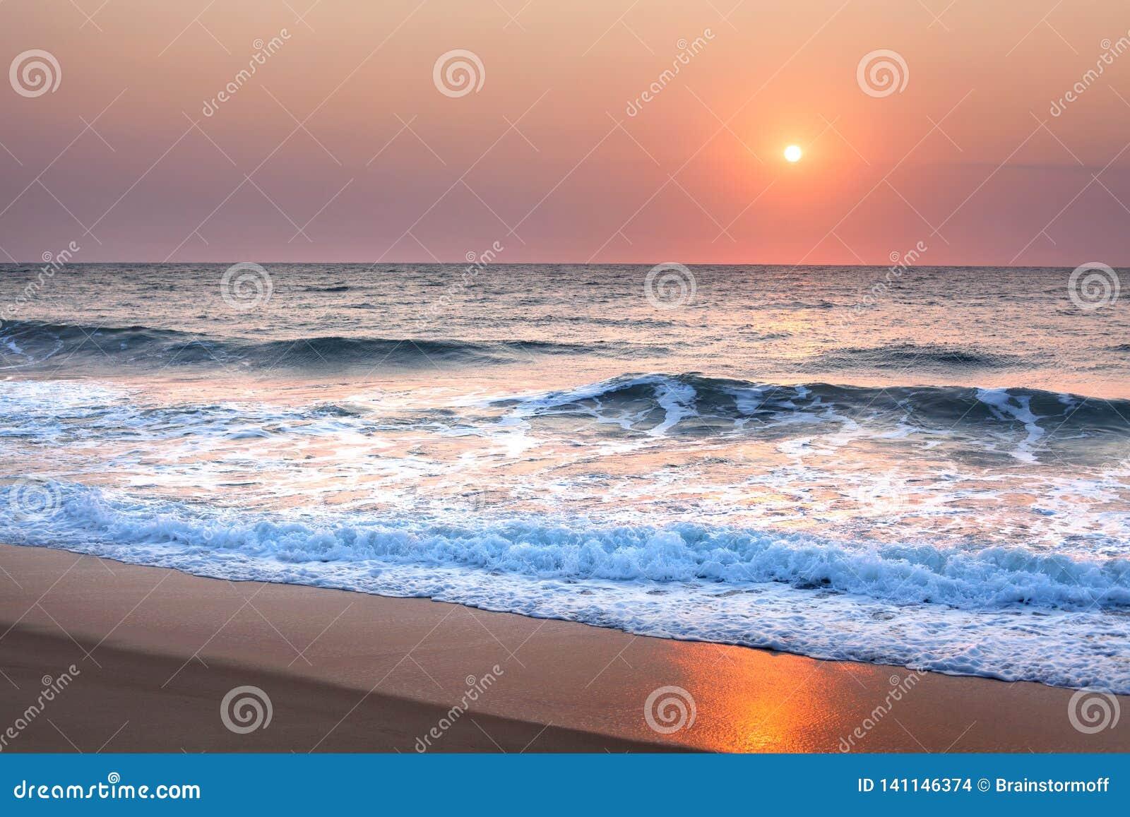 Overweldigende zonsondergang of zonsopgang over het overzees of de oceaan op het strand, de purpere hemel, de blauwe golven, het