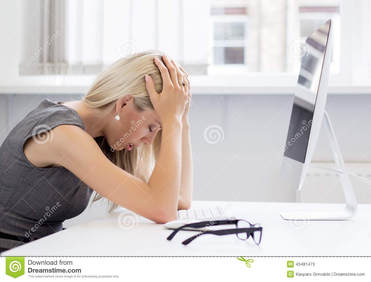 Overworked and frustrated young woman in front of computer