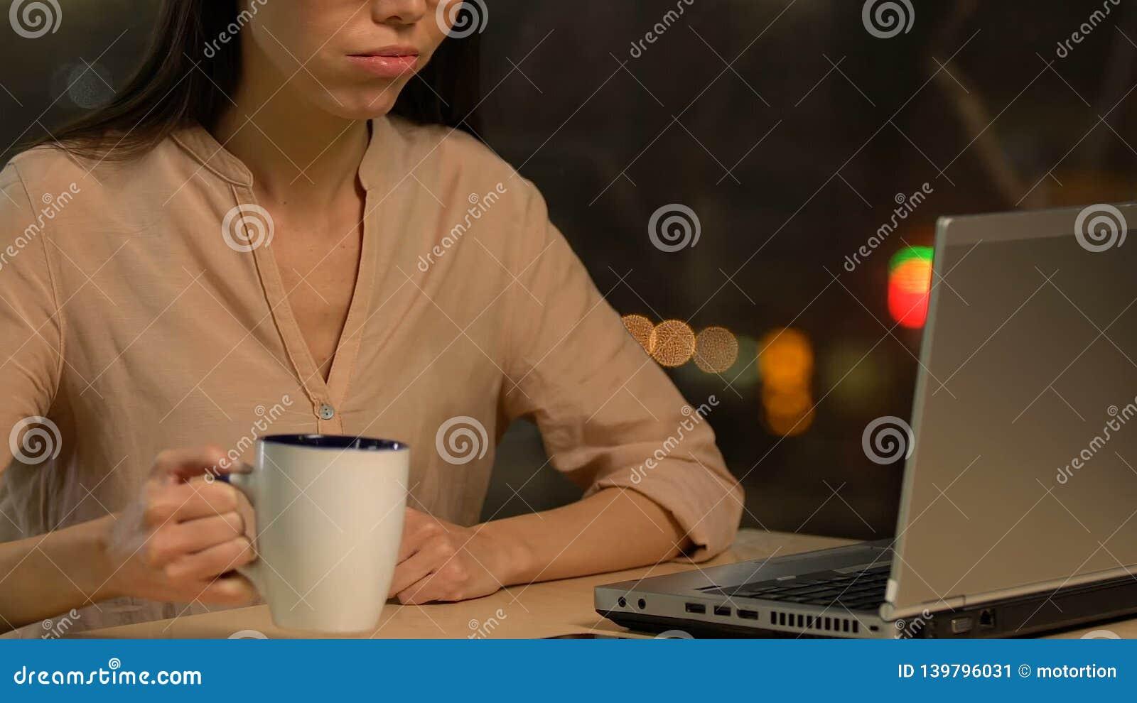 Overworked utmattad dam som arbetar på bärbara datorn och dricker te och att ha inga idéer arkivfilmer