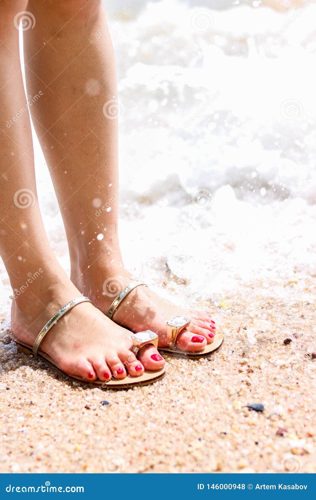 Overzees schuim, golven en naakte voeten op een zandstrand De vakantie, ontspant