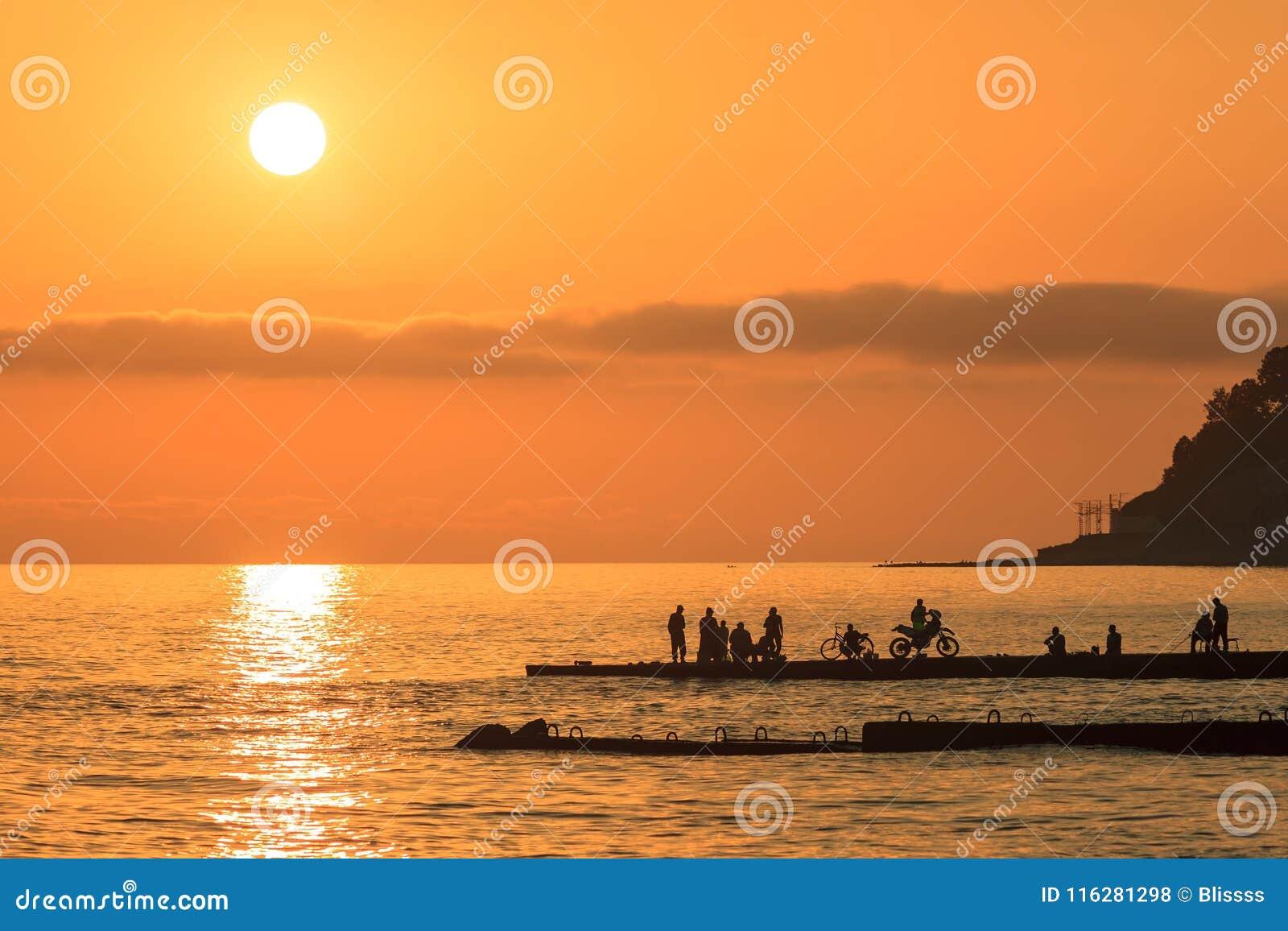 Overzees zonsondergang toneelzeegezicht met verre silhouetten van mensen