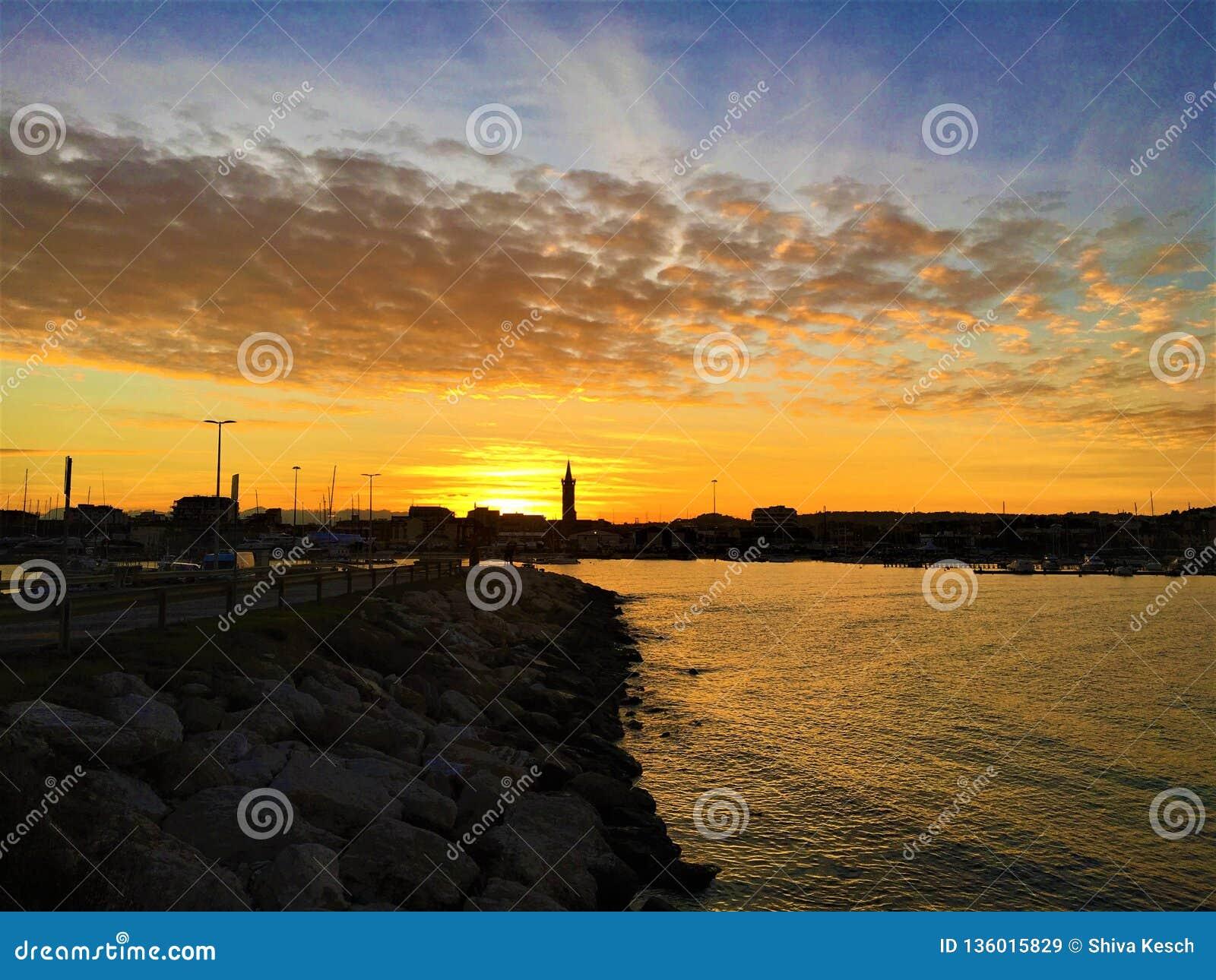 Overzees, zonsondergang, water, hemel en wolken in Civitanova Marche, Italië