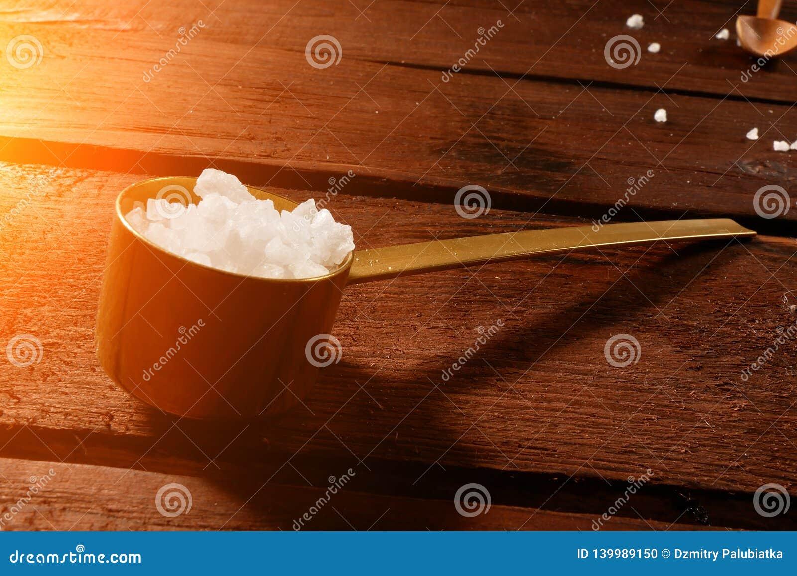 Overzees zout in een lepel op een mooie achtergrond