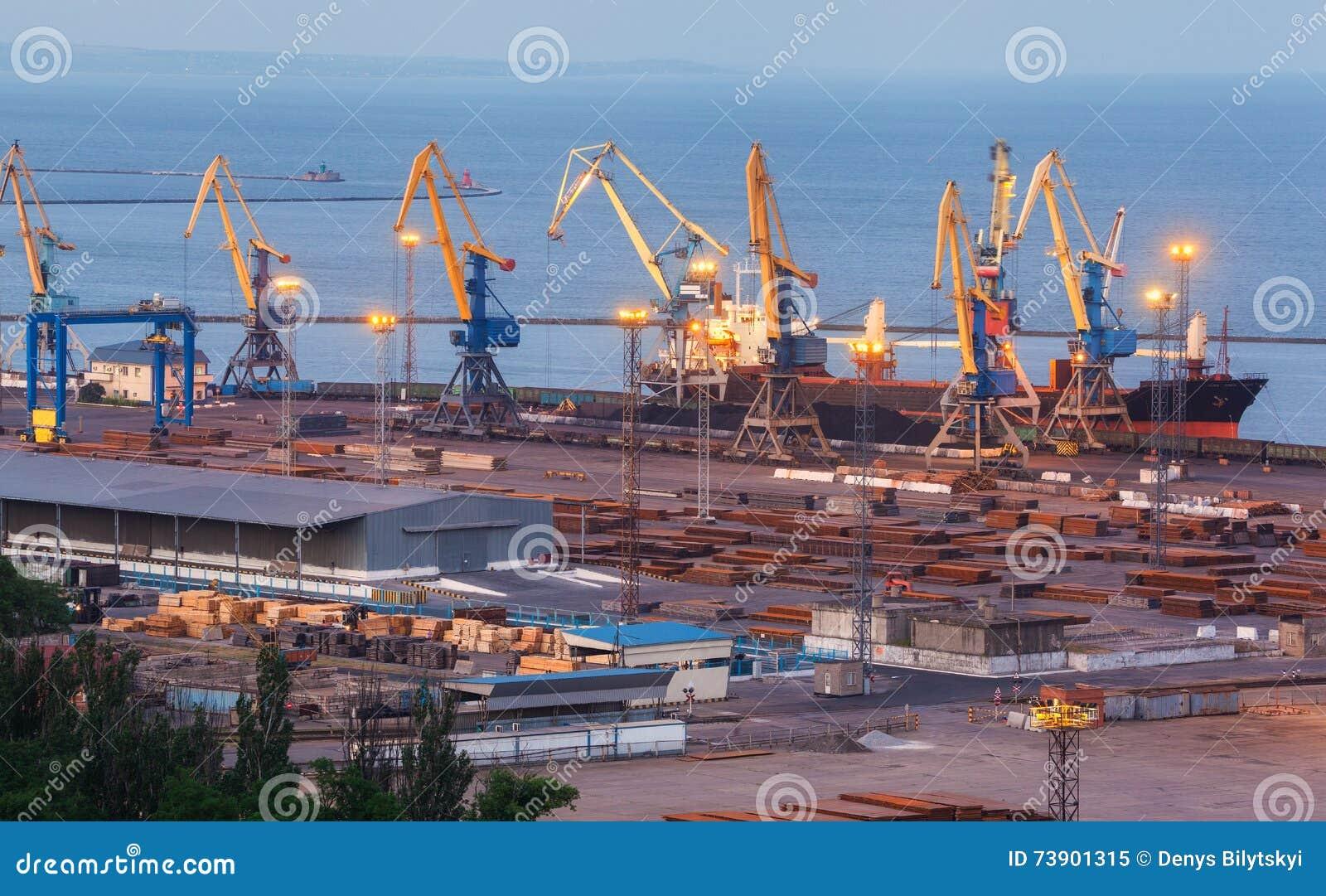 Overzeese commerciële haven bij nacht in Mariupol, de Oekraïne Industriële Mening Het schip van de ladingsvracht met werkende kra
