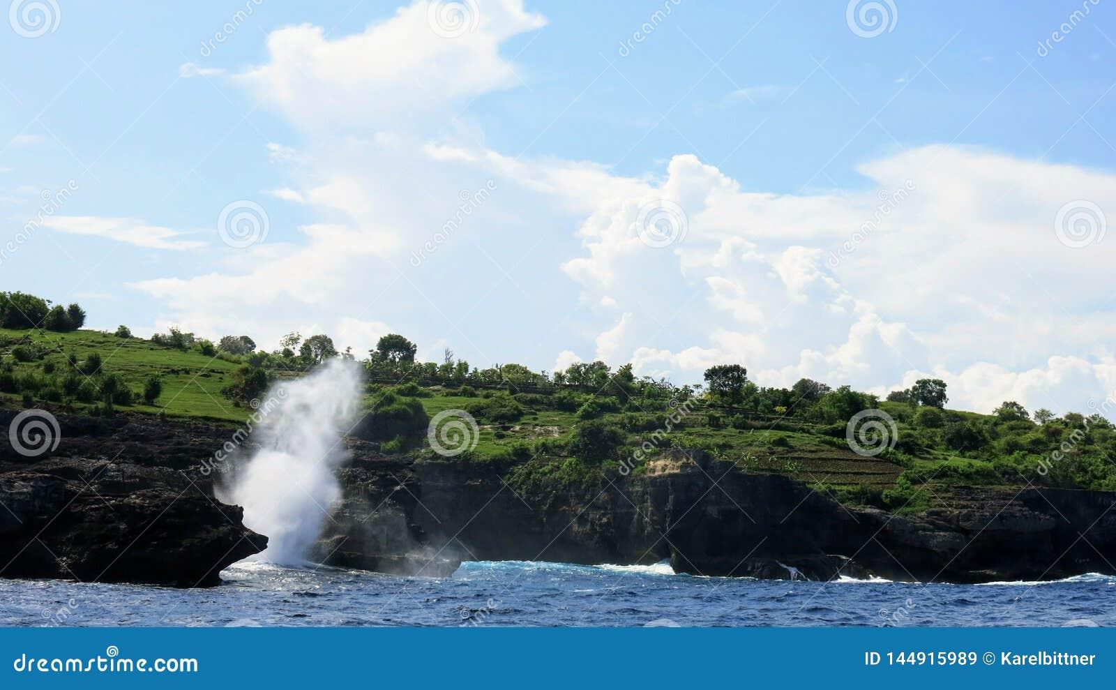 Overzeese golven die tegen de klip van rotsachtige kust van het eiland van Nusa Penida in Indonesië verpletteren