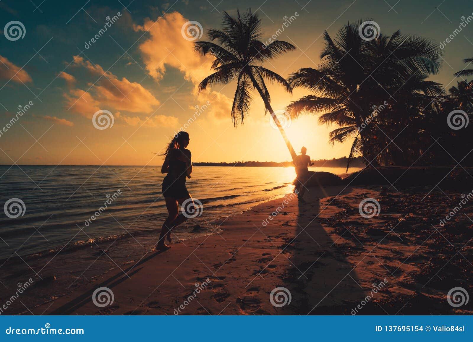Overzeese zonsopgang Meisje die op het tropische eilandstrand Punta lopen Cana
