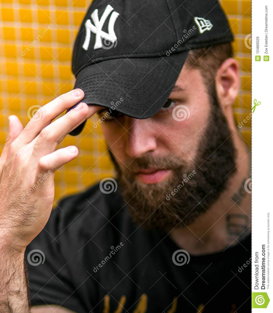 OVIEDO, ASTURIAS. SPAIN -JULY 5, 2018. Portrait of a young hipster tattooed man with New York Yankees hat