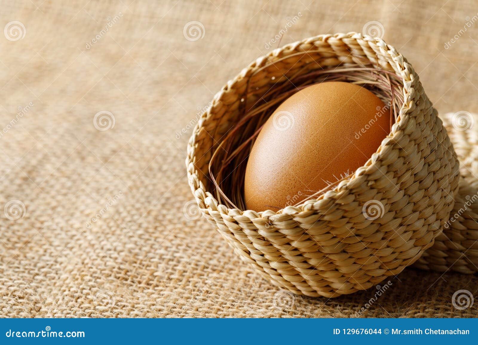 Ovo da galinha ou de galinha na cesta de vime no pano de saco