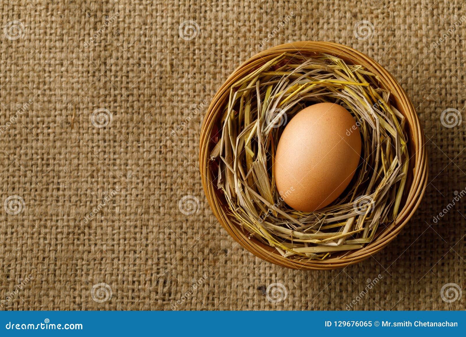Ovo da galinha ou de galinha na palha na cesta de vime no pano de saco