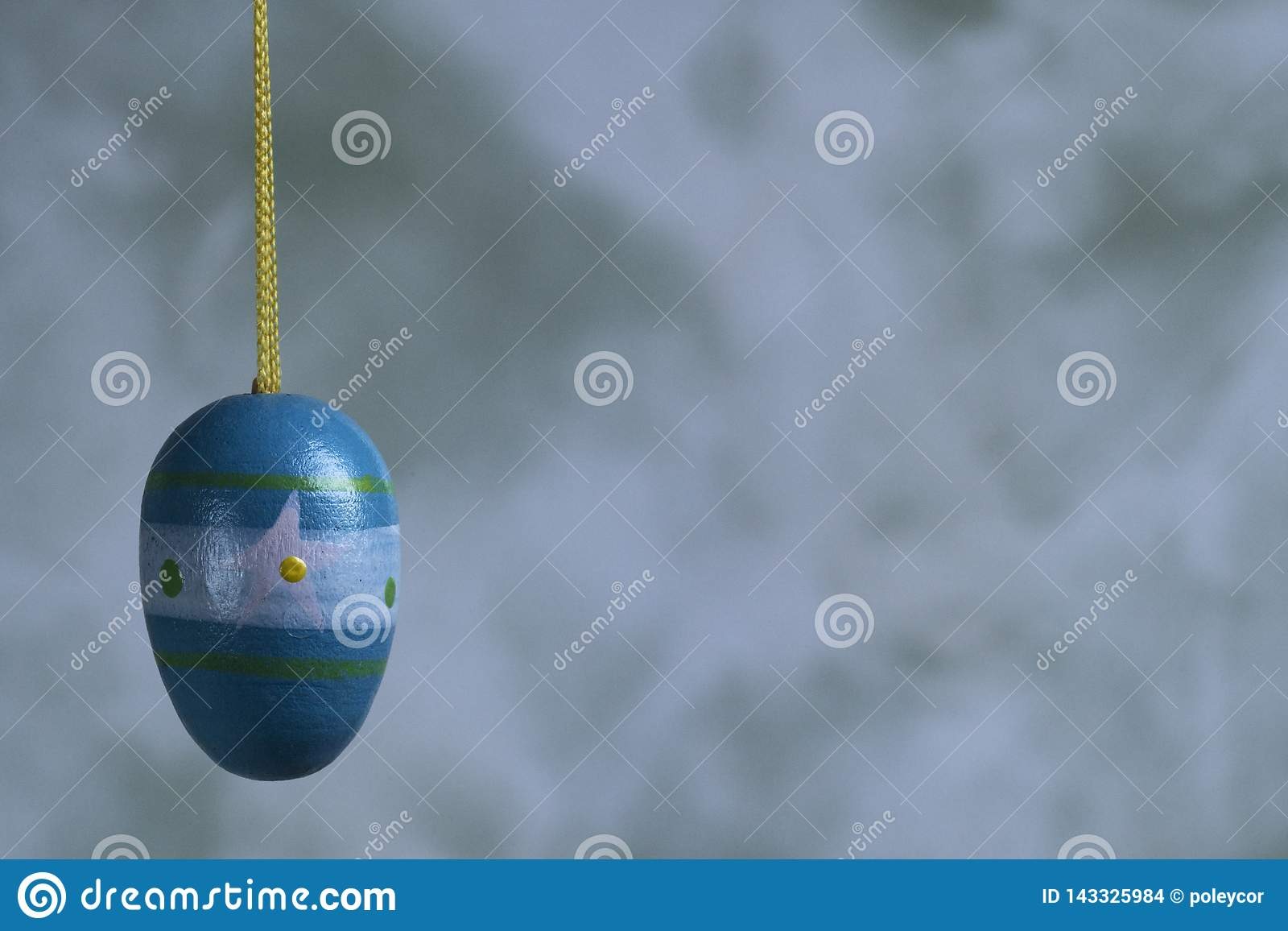 Ovo da páscoa de madeira pintado azul, contra o fundo ardido Espaço para o texto