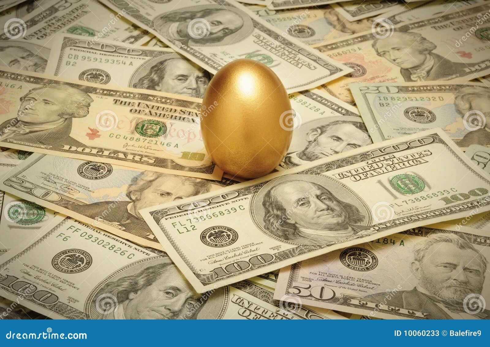 Ovo de ninho do ouro em uma camada de dinheiro