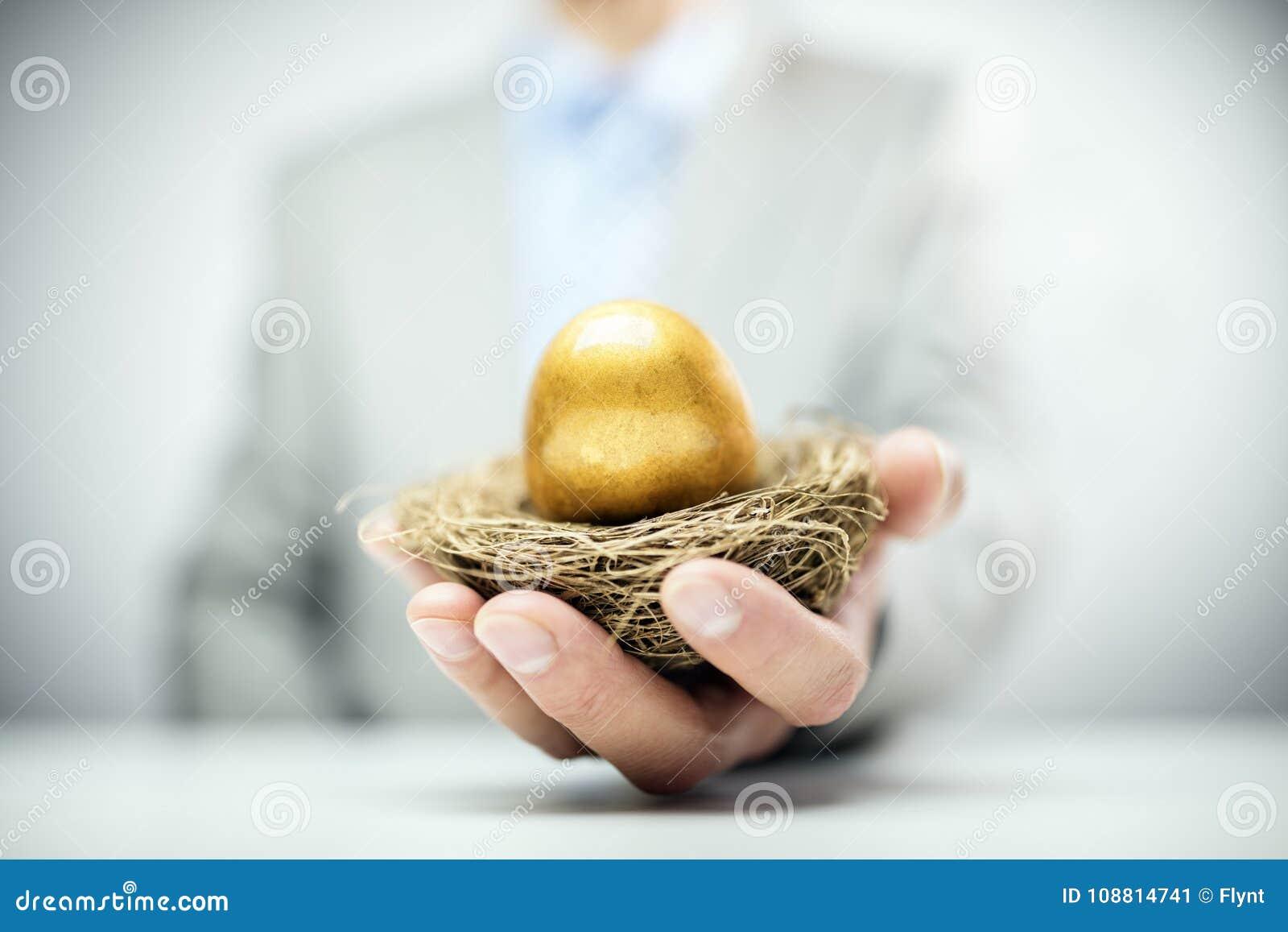 Ovo de ninho dourado das economias da aposentadoria na mão do homem de negócios