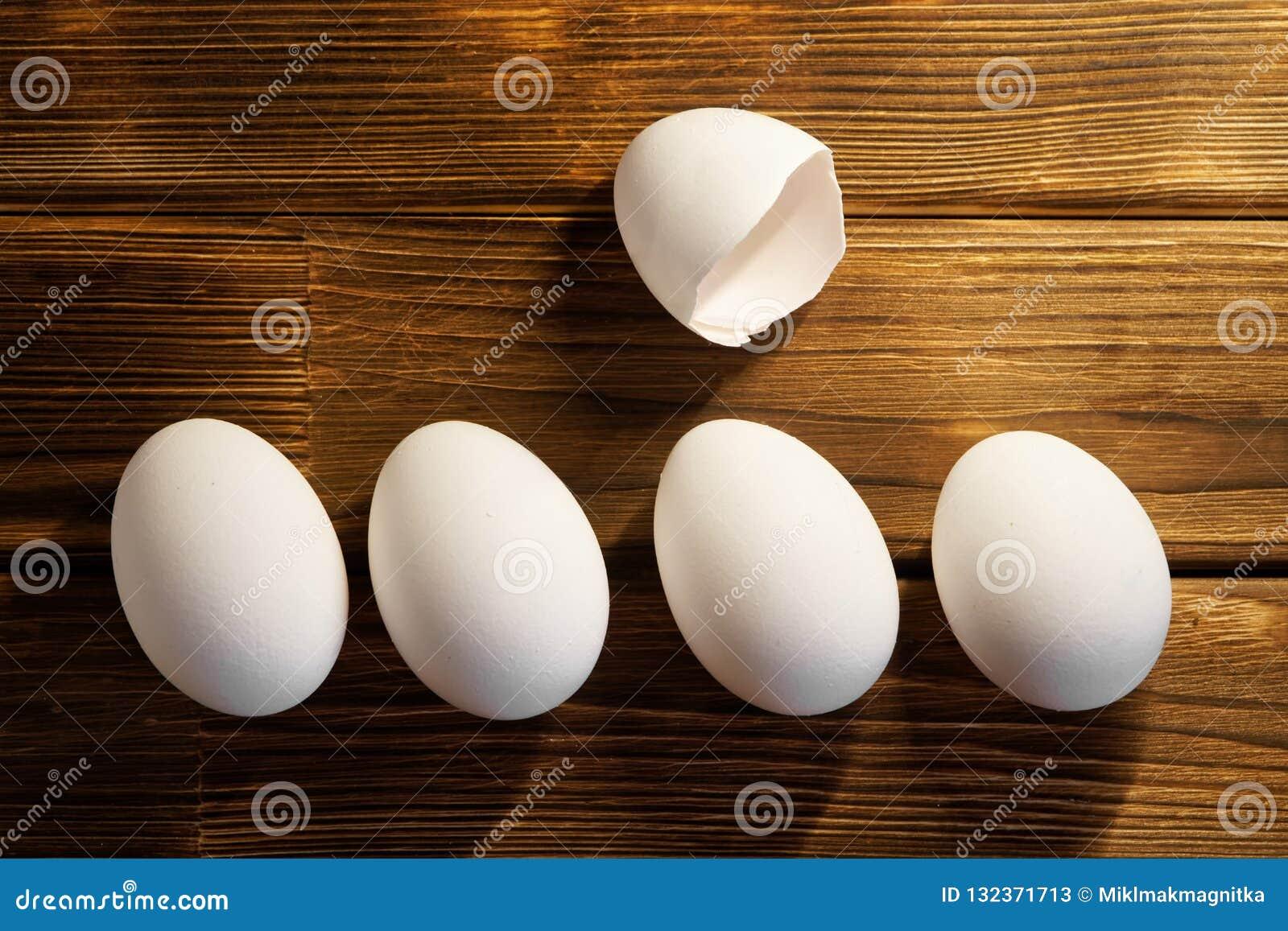 Ovos brancos da galinha em uma tabela de madeira naughty