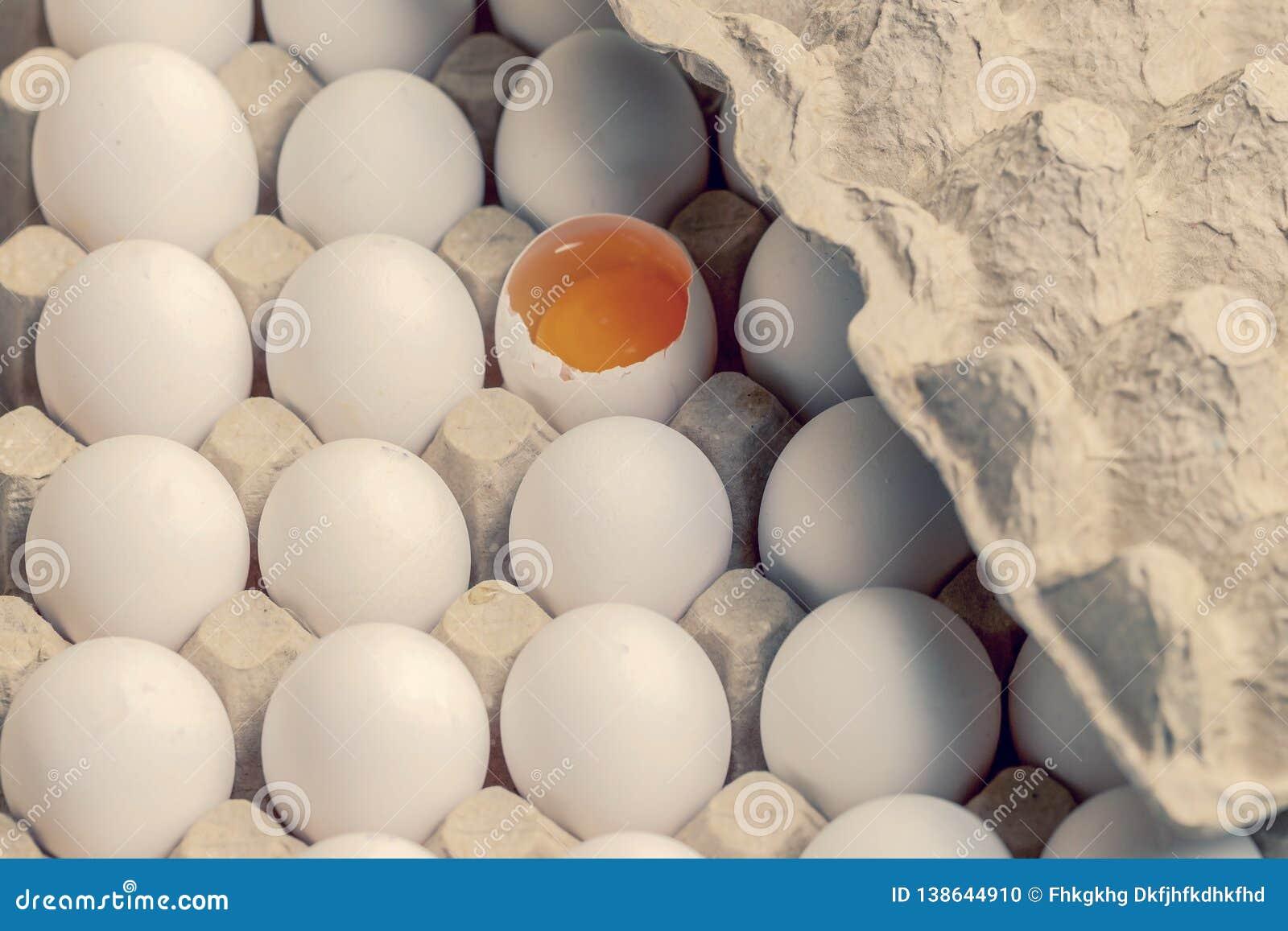 Ovos brancos e marrons na caixa com ovo quebrado