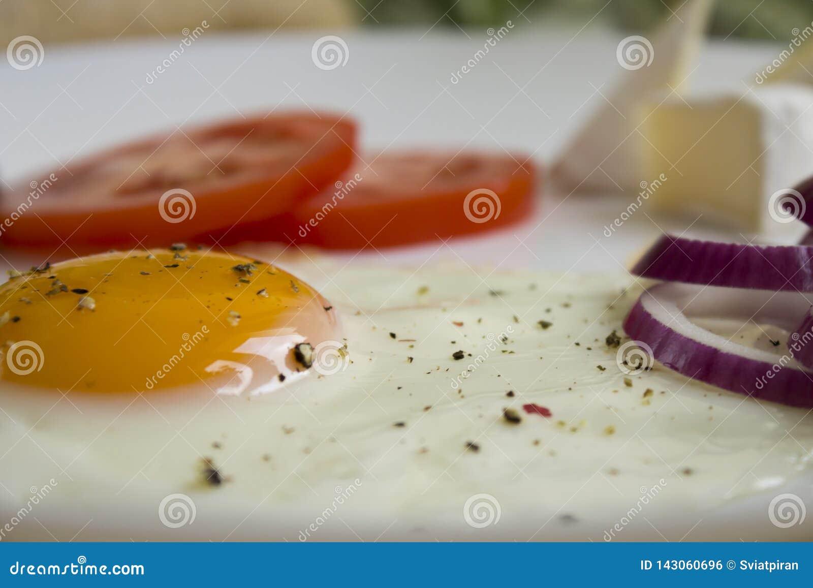 Ovos com um tomate e uma cebola vermelha