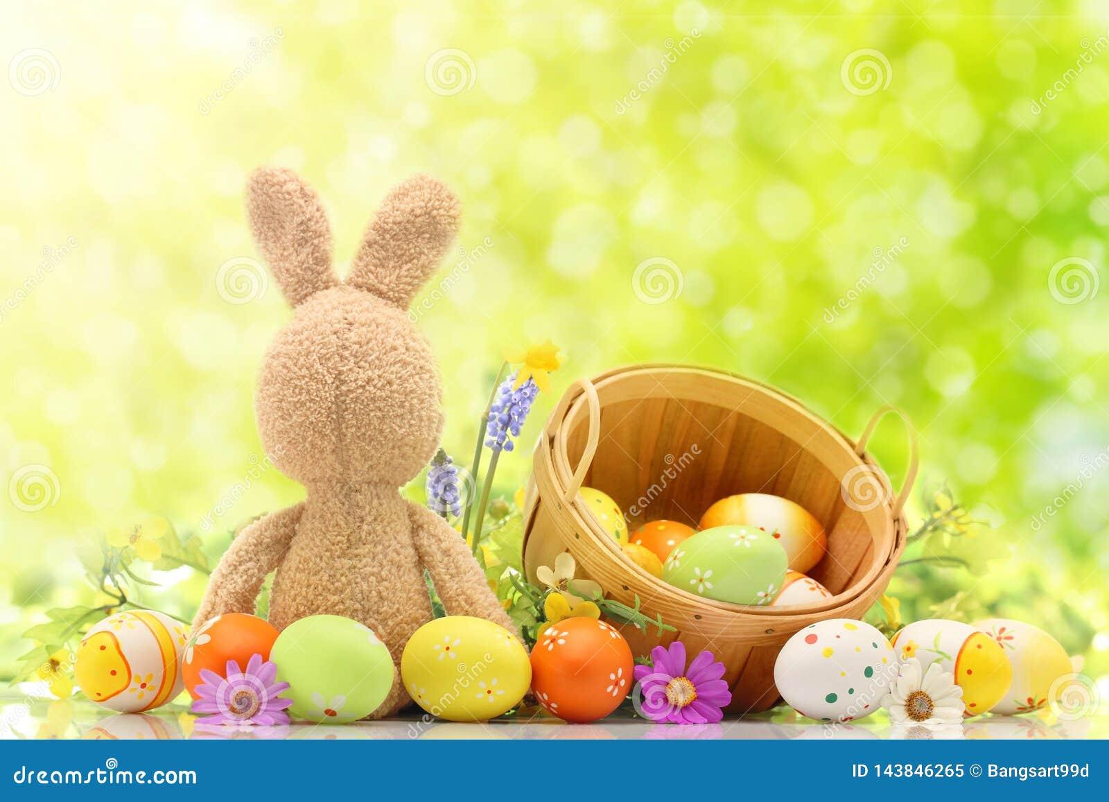 Ovos da páscoa coloridos com coelho de coelho e cesta no meio do fundo verde Espaço livre para o texto