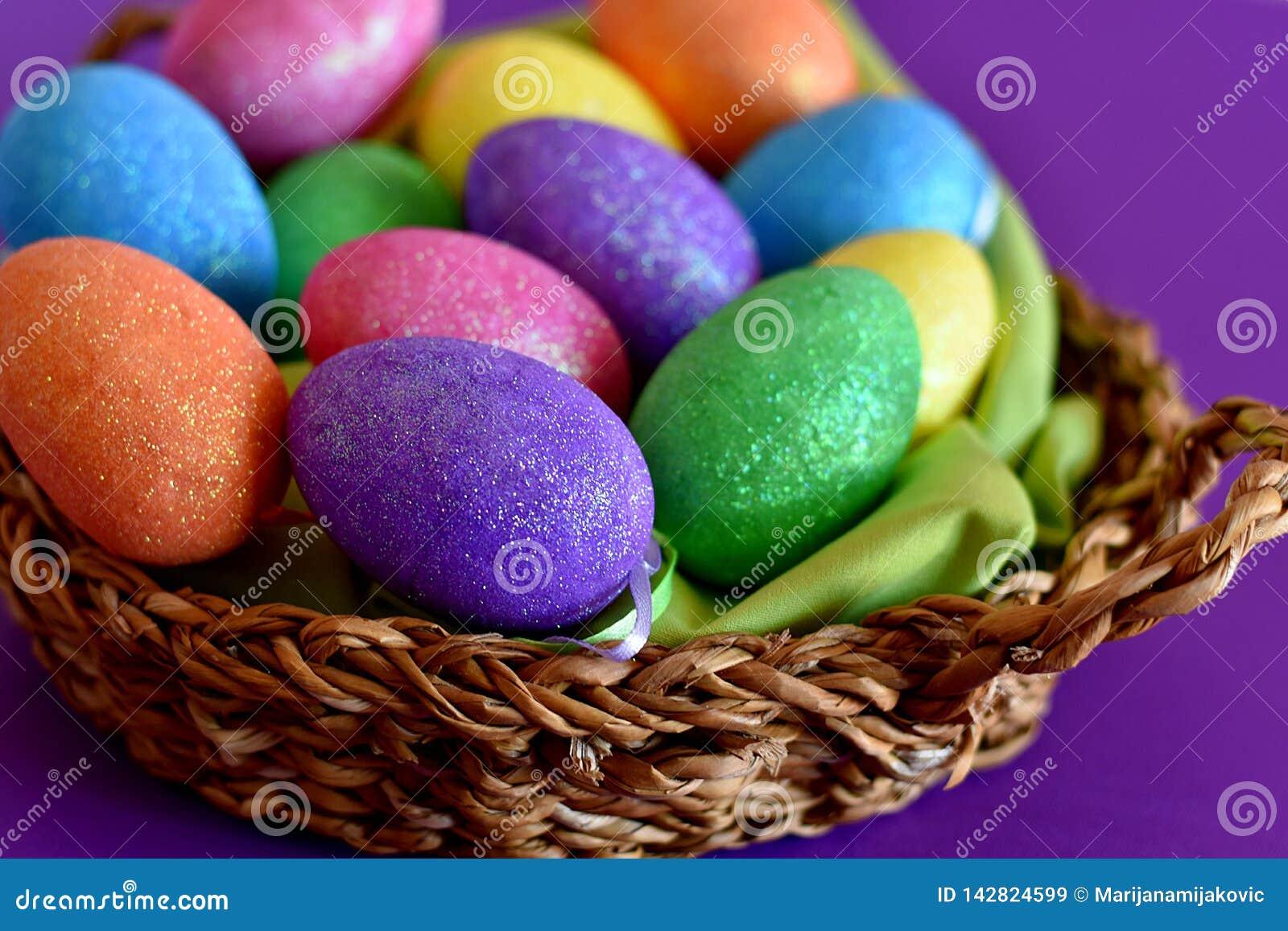 Ovos da páscoa coloridos de brilho efervescentes dos doces em uma cesta de vime