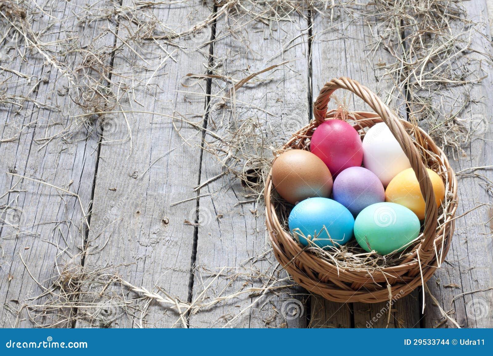 Ovos da páscoa na cesta em pranchas de madeira do vintage