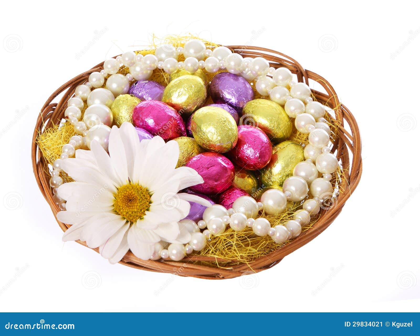 Ovos da páscoa, ovos de chocolate coloridos com flor da camomila e colares da pérola na cesta
