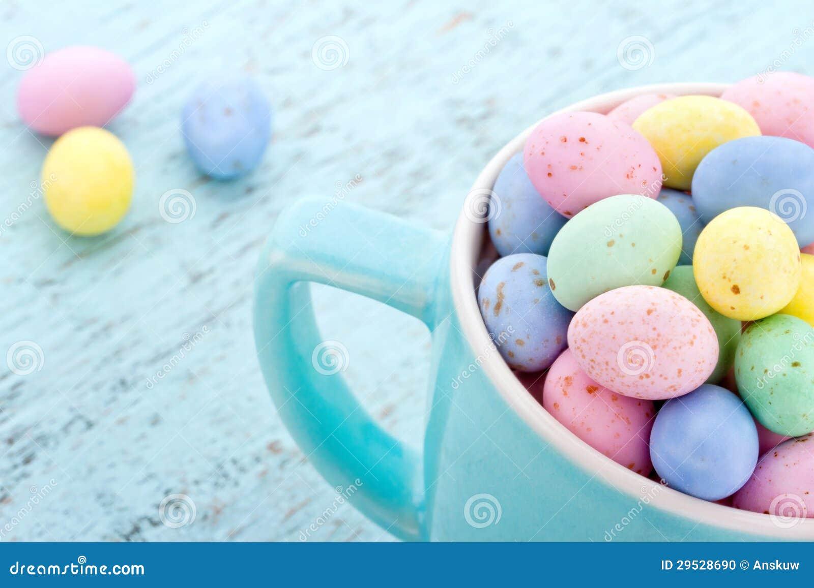 Ovos da páscoa pastel pequenos em um copo azul