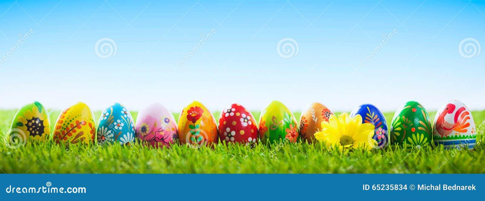 Ovos da páscoa pintados à mão coloridos na grama Bandeira, panorâmico