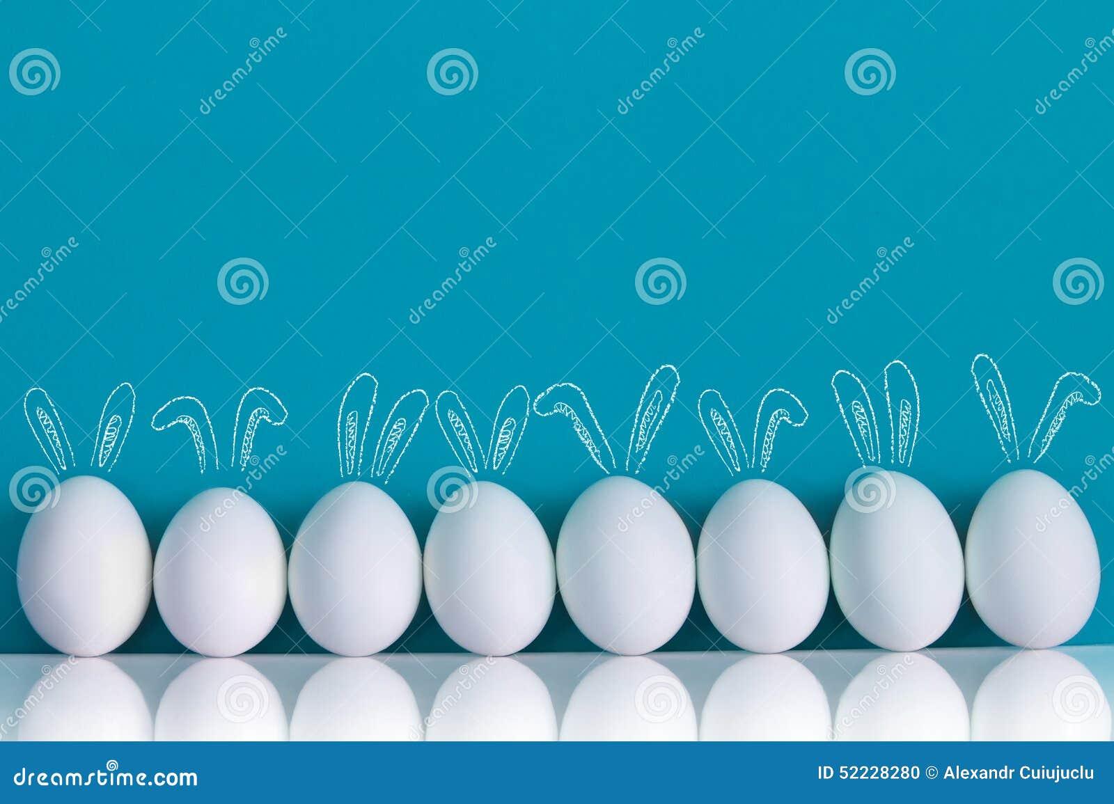 Ovos da páscoa pintados com orelhas de coelhos e ballooons no fundo azul
