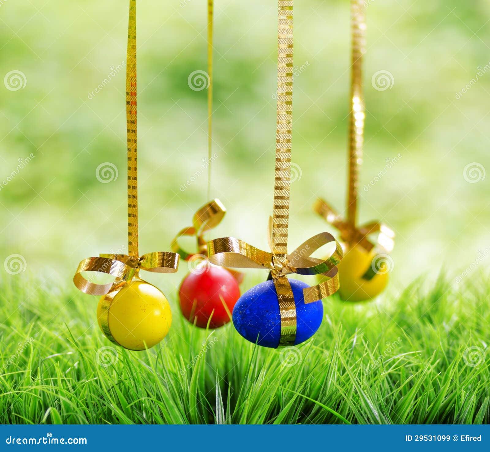 Ovos da páscoa que penduram em fitas douradas