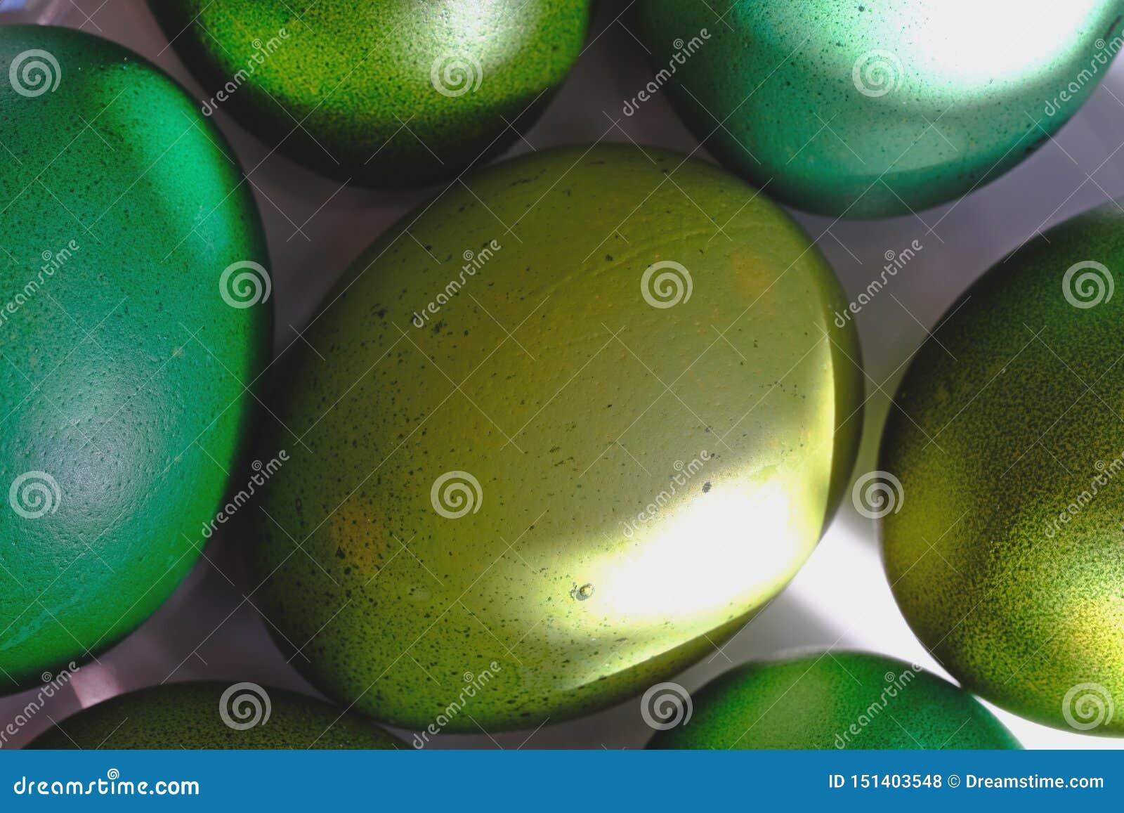 Ovos da páscoa verdes em uma bandeja branca Um raio do sol que brilha no ovo Macro de alta resolução do close up
